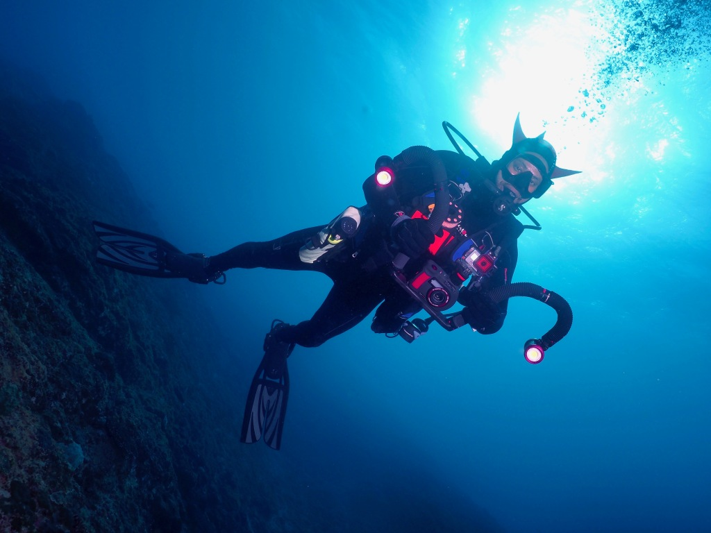 black scuba diver holding sealife camera
