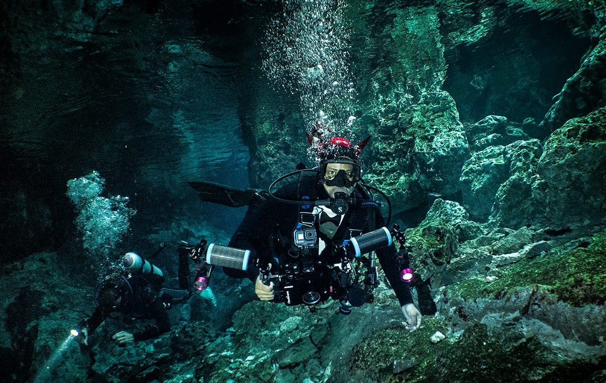 Scuba divers in cenotes Tajma Ha in Mexico