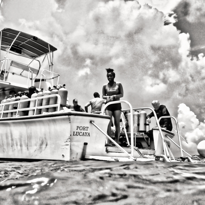 Scuba divers boarding dive boat with help from guide
